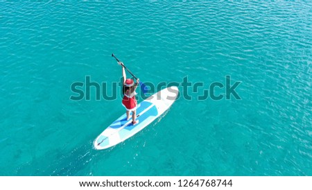Aerial drone photo of fit woman dressed as Santa Claus practising SUP or Stand Up Paddle in tropical turquoise sea  #1264768744