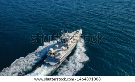 Aerial drone photo of Hellenic Coastguard powerboat cruising in high speed in deep blue Aegean sea #1464891008