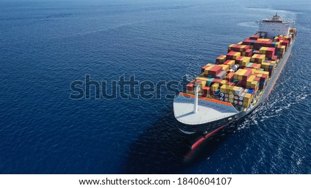 Aerial drone photo of huge container tanker ship carrying truck size colourful containers in deep blue open ocean sea Foto stock ©