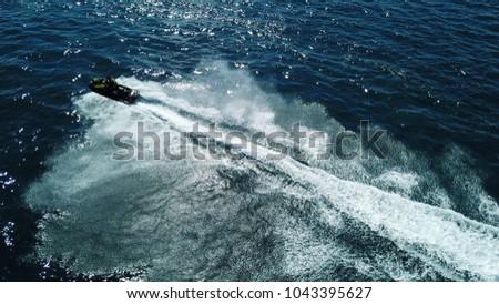 Aerial drone photo of jet ski performing extreme speed acrobatics circling in deep blue mediterranean sea