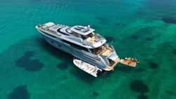 Aerial drone photo of large yacht - boat anchored in tropical exotic paradise bay with emerald open ocean