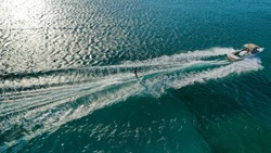 Aerial drone photo of man practicing high speed water ski towed by speed boat in Mediterranean popular destination with emerald clear sea