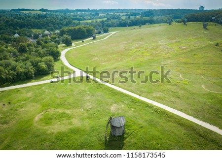 Aerial drone photo of old wooden windmills in green field shot from above #1158173545
