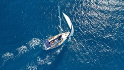 Aerial drone photo of sail boat cruising in the deep blue Aegean sea, Cyclades, Greece