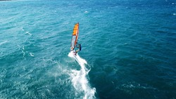 Aerial drone photo of surfer cruising in high speed in mediterranean open wavy  sea