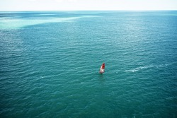 Aerial drone photo of surfer cruising in sea. Sport and leisure. Windsurfer sailing on windsurf board.