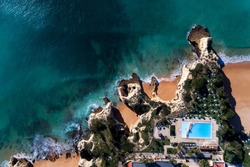 Aerial drone photo of the beautiful coastline near the Senhora da Rocha beach near Lagoa, in Algarve, with a swimming pool on the cliffs, in Portugal