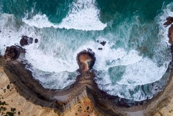 Aerial drone photo of the waves crashing against the rocks in the beautiful coastline along the Vicentine Coast, near the Bordeira Beach, in Algarve, Portugal