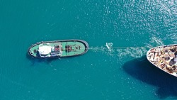 Aerial drone photo of tow boat cruising in mediterranean port