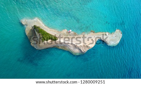Aerial drone photo of tropical exotic small island with white volcanic rock and deep turquoise and sapphire clear open ocean sea