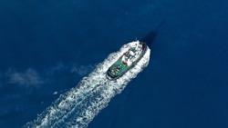 Aerial drone photo of tug boat cruising Mediterranean port