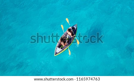 Aerial drone photo of 2 women canoeing in tropical caribbean turquoise sea