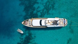 Aerial drone photo of yacht anchored in popular bay and beach of Super Paradise, Mykonos island, Cyclades, Greece