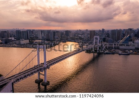 Aerial drone photo - Rainbow Bridge and the skyline of Tokyo at sunset.  Capital city of Japan.