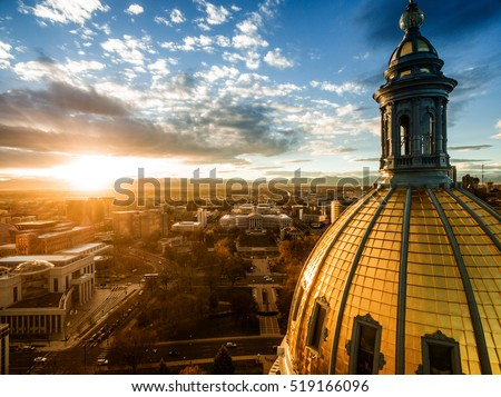 Aerial/Drone photograph of a sunset over the Colorado state capital building in Denver.  The Rocky Mountains can be seen on the horizon