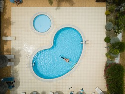 Aerial drone picture about a beautiful, blue ,outdoor swimming pool with playing children.