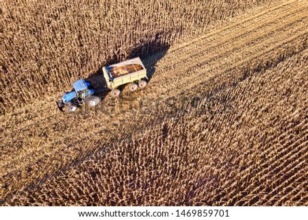 Aerial Drone Scene of a Tractor with Chaser Bin Full of Crop in a Partly Harvested Corn Field #1469859701