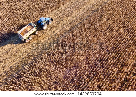 Aerial Drone Scene of a Tractor with Chaser Bin Full of Crop in a Partly Harvested Corn Field