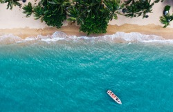 Aerial drone scenery of coastline with turquoise water waves and green tropical palms. Bird's eye view of paradise beach with boat near shoreline of Hawaii, destination for summer vacations