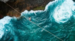 Aerial Drone Scenic Adventure Sport Portrait of a Mindfulness Slackliner Man Crossing a Tightrope in a Very Secret Cliff w. Giant Green Waves of Paradisiac Atlantic Ocean Rare Beach Next Vidigal Slum