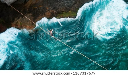 Aerial Drone Scenic Adventure Sport Portrait of a Mindfulness Slackliner Man Crossing a Tightrope in a Very Secret Cliff w. Giant Green Waves of Paradisiac Atlantic Ocean Rare Beach Next Vidigal Slum