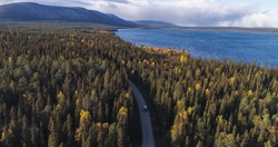 Aerial, drone shot of a Camper van in foliage forest, lake Pallasjarvi and Ounastunturit fells, autumn day, in Pallas-Yllas park, Lapland, Finland