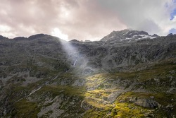 Aerial drone shot of sun light through overcast clouds on top of Zillertal Alps in Austria