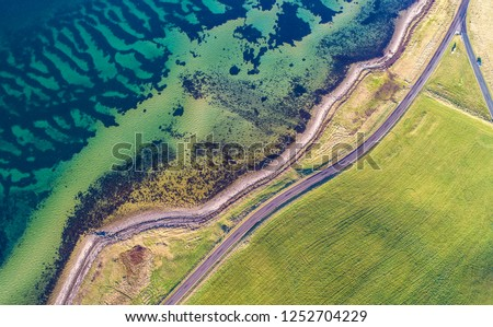 Aerial drone shot of the eastern coastline of Denmark, green grass field with a road on the right and the coastline with clear blue water on de left taken from above, wide birds eye view landscape  #1252704229