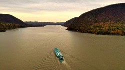 aerial drone shot over the Hudson River in Beacon, NY on a cloudy evening just before sunset. There is a turquoise colored tug boat & barge sailing by below