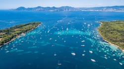 Aerial drone shot view of yachts between Ile Sainte Marguerite and Ile Saint Honorat in mediterranean sea