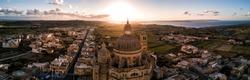 Aerial drone sunrise panorama - Rotunda St. John Baptist Church in the town of Xewkija, Gozo.  Country of Malta.  Mediterranean Sea on the horizon