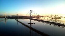 Aerial drone sunrise view of The Queensferry Crossing bridges over the Firth of Forth, Edinburgh, Scotland, UK.