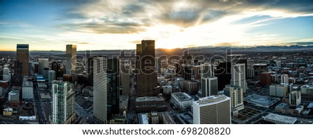 Aerial Drone Sunset Panorama - Skyline of the city of Denver, Colorado.  Rocky Mountains are on the horizon.