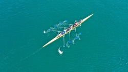 Aerial drone top down bird's eye view photo of yellow sport canoe operated by team of young team in emerald clear sea