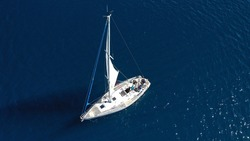 Aerial drone top down photo of beautiful sail boat cruising in deep blue Aegean sea