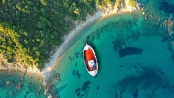 Aerial drone top down photo of beautiful wooden red fishing boat anchored in paradise bay covered with pine trees, Skiathos island, Sporades, Greece