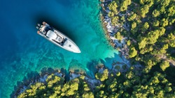 Aerial drone top down photo of inflatable speed boat anchored in tropical exotic island covered with pine trees
