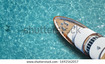 Aerial drone top down photo of luxury exotic yacht nose with wooden deck anchored in paradise turquoise bay