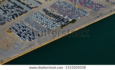 Aerial drone top down photo of new cars lined up in automobile port terminal for import and export #1553205038