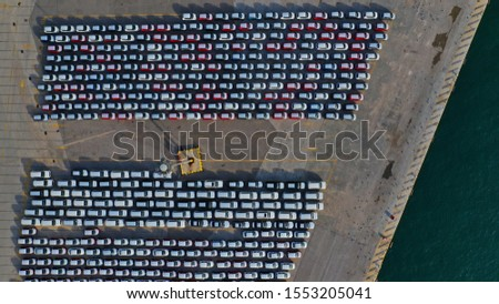 Aerial drone top down photo of new cars lined up in automobile port terminal for import and export #1553205041