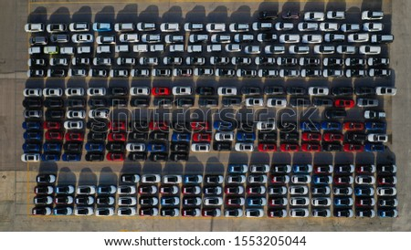 Aerial drone top down photo of new cars lined up in automobile port terminal for import and export #1553205044