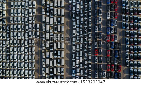 Aerial drone top down photo of new cars lined up in automobile port terminal for import and export #1553205047