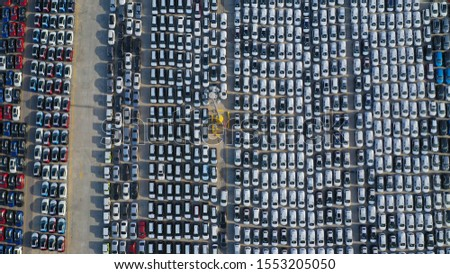 Aerial drone top down photo of new cars lined up in automobile port terminal for import and export #1553205050