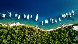Aerial drone top down photo of sail boats and yachts anchored in traditional fishing village of Fiskardo, Kefalonia island, Ionian, Greece