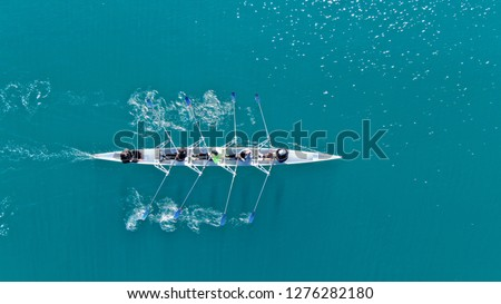 Aerial drone top down photo of sport canoe operated by team of young women in emerald calm sea waters