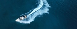Aerial drone top down ultra wide photo of inflatable power rib boat making extreme manoeuvres in Mediterranean bay with deep blue sea at dusk
