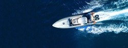 Aerial drone top down ultra wide photo of inflatable speed boat with wooden deck cruising in high speed in deep blue Aegean sea