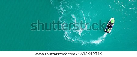 Aerial drone top down ultra wide photo of jet ski watercraft cruising in low speed in tropical exotic lake with calm emerald waters Сток-фото ©