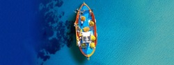Aerial drone top down ultra wide photo of traditional fishing boat docked in Ionian deep turquoise sea, Greece
