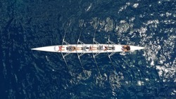 Aerial drone top down view of sport canoe operated by team of young trained athletes in deep blue Aegean sea
